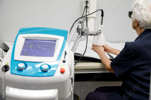Photo Physiotherapy device treats arthritis and arthrosis, on the hands of an elderly