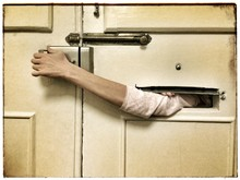 Man Unlocking Door Through Mail Slot