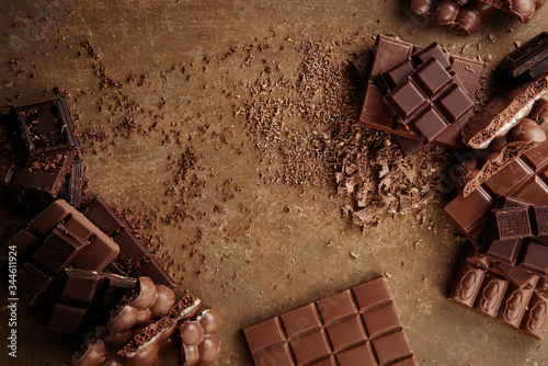 Fototapeta Composition of bars and pieces of different milk and dark chocolate, grated cocoa on a brown background top view close up obraz