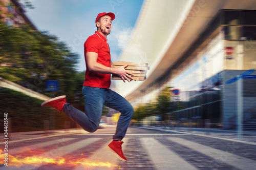 Fényképezés Messenger in red uniform runs on foot really fast to deliver quickly hot pizzas