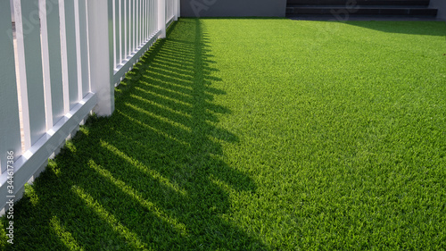 Fotomural Sunlight and shadow of white wooden fence on green artificial turf surface in fr