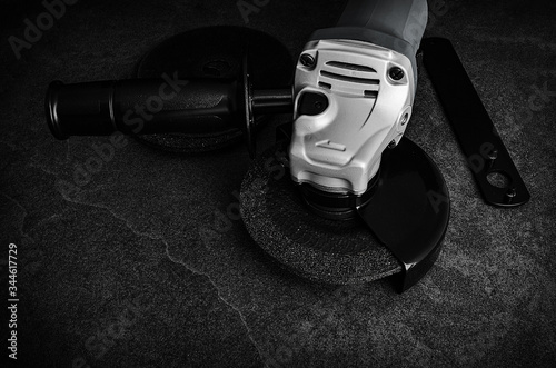 Photo Low Key view of an angle grinder on concrete floor with accessories