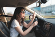 Portrait of aggressive brunette woman showing middle finger to somebody while driving a car.