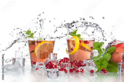 summer pomegranate drink with lemon and mint with splashed water and ice