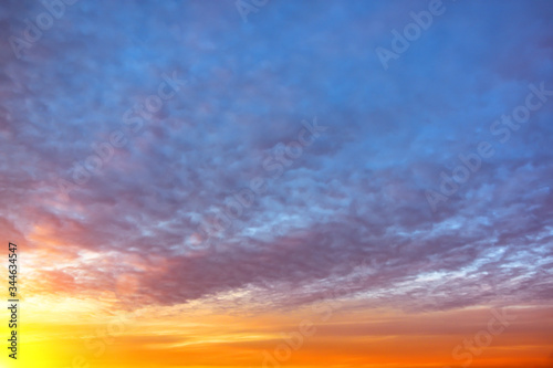 Cirrus evening clouds backlit by the sun, sky view. Canvas Print