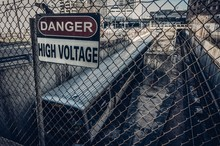 High Voltage Sign On Chainlink Fence By Train In City