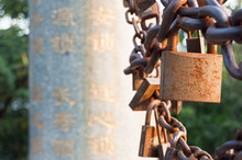 Close-up Of Rusty Padlocks With Chain By Column