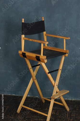 Fotografie, Obraz A filmmakers chair with wooden legs and a black seat stands against a gray-blue