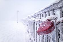 Padlocks On Railing Of Snow Covered Bridge Against Sky