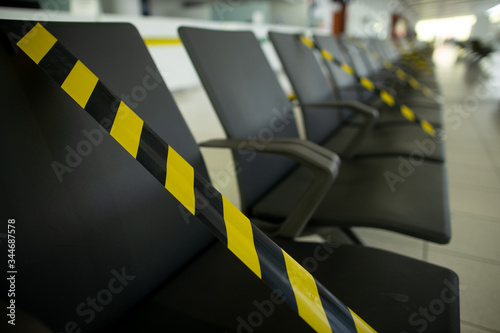 Yellow and black warning sign taping marked on public chairs 1 Wallpaper Mural