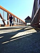 Woman Walking On Footbridge Against Sky