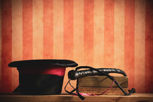 A Top Hat And Whip, Tools Of A Lion Tamer. With A Circus Or Carnival Style Stripe Background.