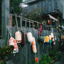Various Fishing Bobbers On Fence