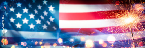 Fotografia Close-up Of Sparkler With Bokeh And Smoke On American Flag Background - Independ