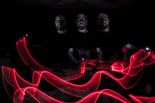 Multiple Image Of Serious Man By Red Light Painting Against Black Background
