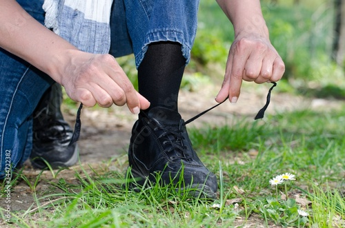 Fotografía Closeup shot of a male's hands tying his shoelace on the grass-covered field
