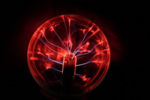 Close-up Of Red Plasma Ball Against Black Background