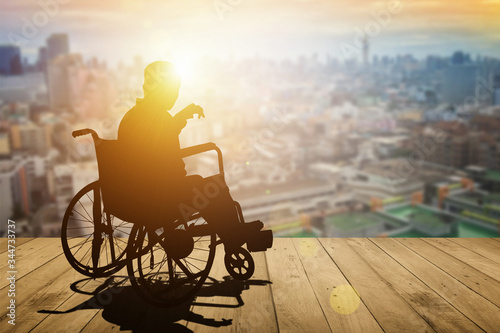 Obraz Disabled person silhouette with hand lift on wheelchair have sunset city background. International Disability Day or Handicapped sport or Paralympics. Challenge and Conquer success and health concept. - fototapety do salonu
