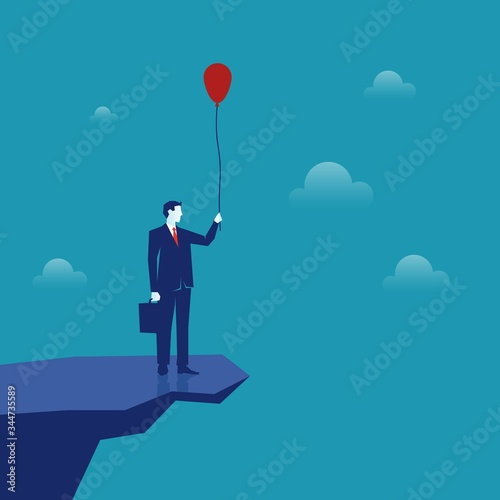 startBusinessman on a cliff above an abyss holding a balloon. Canvas Print