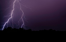 Lightning Over Silhouette Field Against Sky At Night