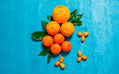Top view mandarin orange with leaves on blue textured background. horizontal