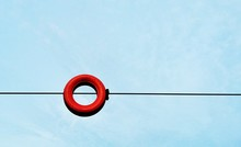 Low Angle View Of Red Tire On Cable Against Blue Sky