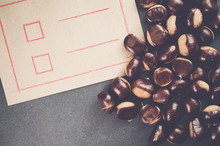 Close-up Of Chestnuts By Paper On Slate