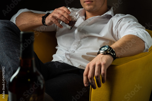 Fényképezés brutal man holds a glass of whiskey in his hands