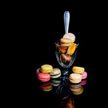 Macarons Colorés Dans Un Verre Avec Une Cuillère Sur Fond Noir