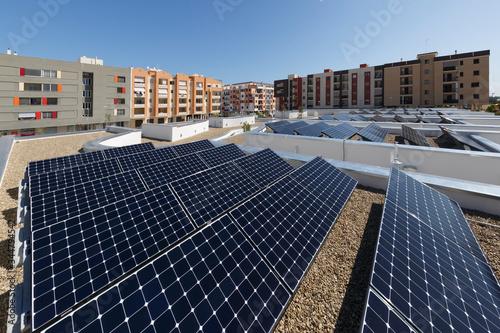 Pannelli fotovoltaici sopra il tetto di un palazzo, intorno altri palazzi Canvas Print