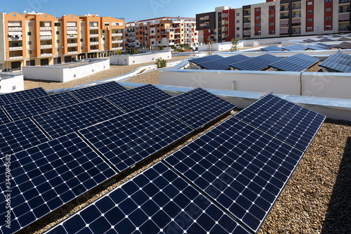 Photo Pannelli fotovoltaici sopra il tetto di un palazzo, intorno altri palazzi