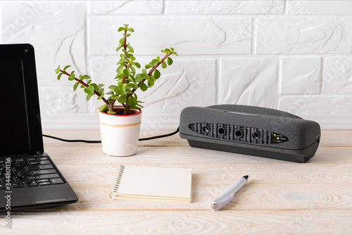 Black air ionizer near laptop on a white wooden table Wallpaper Mural