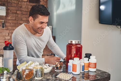 Photo Dark-haired sportsman making a list of dietary supplements