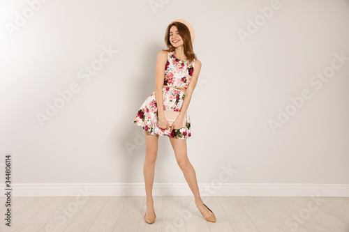 Fotografie, Obraz Young woman wearing floral print dress with clutch purse near light wall