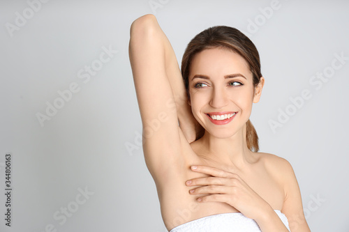Young woman showing armpit with smooth clean skin on light grey background Wallpaper Mural