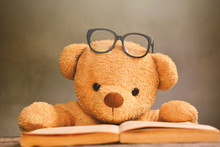 Teddy Bear With Eyeglasses By Book On Table Against Wall