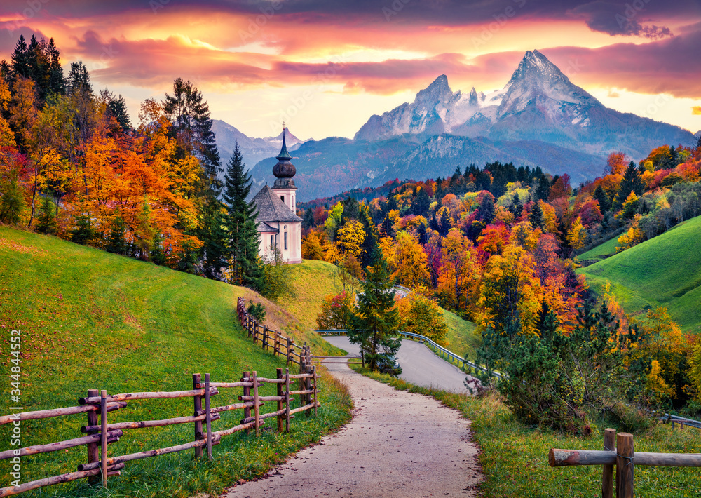 Fototapeta Iconic picture of Bavaria with Maria Gern church with Hochkalter peak on background. Fantastic autumn sunrise in Alps. Superb evening landscape of Germany countryside. Traveling concept background..
