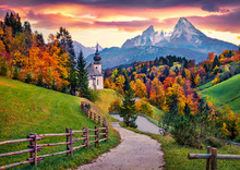 Iconic Picture Of Bavaria With Maria Gern Church With Hochkalter Peak On Background. Fantastic Autumn Sunrise In Alps. Superb Evening Landscape Of Germany Countryside. Traveling Concept Background..