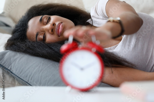 Portrait of sleepy brunette lying on comfortable bed Canvas Print