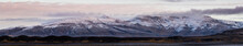 A Panorama And Wide Angle Shot Of Snow Capped Rocky Mountains Located On The Edge Of Hvalfjordur, Iceland. Wispy Clouds Cover The Peaks As The Sun Rises Lighting The Mountainside.