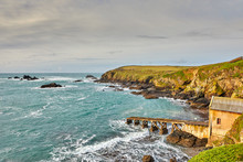 Image Of The Bay And Former Life Boat Station At Lizard Point, Cornwall, With An Overcast Sky.