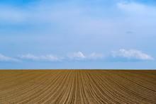 Beautiful Shot Of A Freshly Plowed Farm Field On A Blue Sky Background