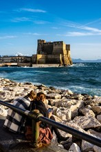 Vertical Shot Of Two Young People Seating On A Rocky Beach On A Background Of The Castel Dell' Ovo