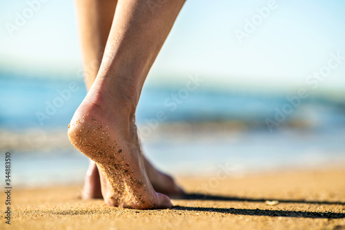 Photo Close up of woman feet walking barefoot on sand leaving footprints on golden beach