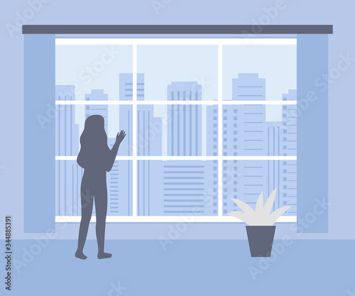 Woman stands at home and looks out of window at city Canvas Print