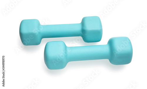 Fotografia Two turquoise colored rubber dumbbells lying at white table