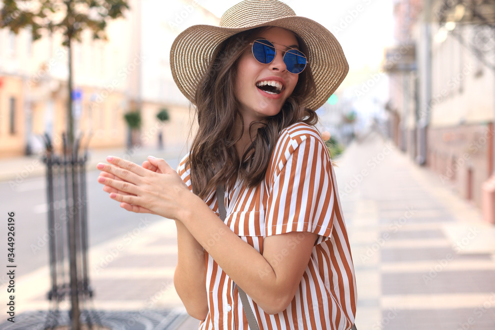 Fototapeta Portrait fashion woman is posing in the city, summer street fashion. Laughing and smiling portrait.