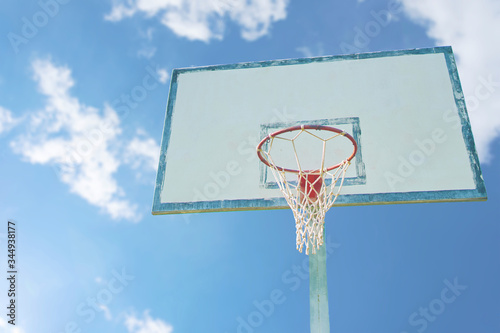 Basketball backboard and basket with cloud on bright blue sky background Canvas Print