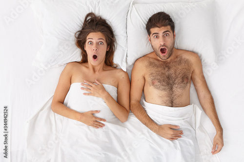 Photo Overhead shot of emotional shocked woman and man stay in bed covered by sheet, stare with wide opened mouth, overslept work or flight