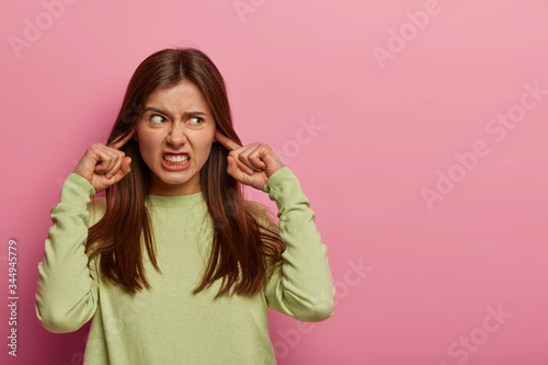 Photo Resentful annoyed woman plugs ears, irritated with loud noise, avoids annoying s